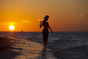 A Silhouette of a Woman Wearing a Hat Walking in the Surf at Sunset on Holbox Island, Mexico by Karine Aigner
