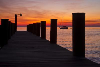 Sunrise on the Water with an Empty Dock and a Sailboat in the Distance of Tilghman Island, Maryland