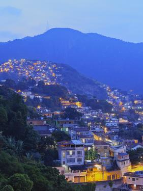 Twilight view of the favelas Unidos de Santa Teresa Morro do Escondidinho and Morro dos Prazeres, R by Karol Kozlowski