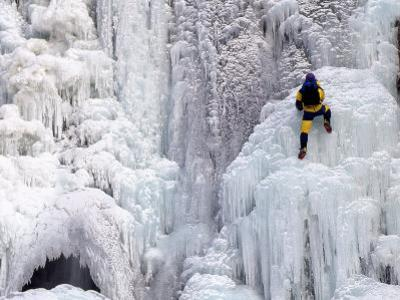 Ice Climber Climbing a Frozen Waterfall, Tangle Creek, Rocky Mountains, Canada