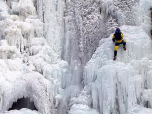 Ice Climber Climbing a Frozen Waterfall, Tangle Creek, Rocky Mountains, Canada by Kate Thompson