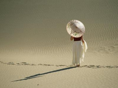 Lady with Parasol Standing in Sand Dunes and Casting a Shadow