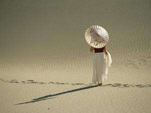 Lady with Parasol Standing in Sand Dunes and Casting a Shadow by Kate Thompson