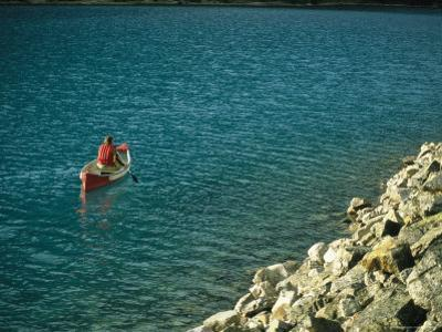 Man Canoeing on Placid Waters of Lake Louise
