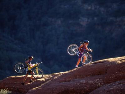 Two Women Carry their Bikes Up a Petrified Sandstone Dune