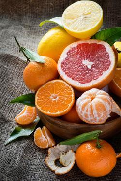 Fresh Citrus Fruits on Rustic Background by katerinabelaya