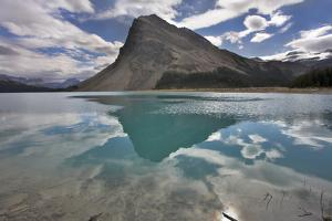 The Huge Rock Of The Triangular Form Is Reflected In Emerald Waters Of Cold Mountain Lake by kavram