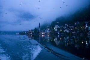 A fishing boat's wake on the Hallstattersee and Hallstatt at dawn. by Keenpress