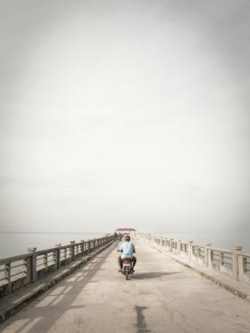 A Motorcyclist Drives Down a Pier on the Andaman Sea by Keith Barraclough