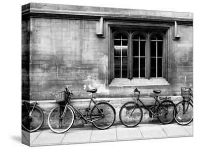 A Row of Bikes Leaning Against an Old School Building in Oxford, England by Keith Barraclough