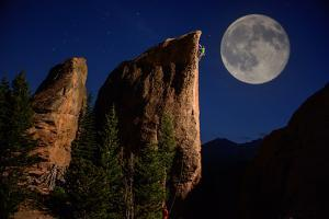 A Climber Ascends a Rock Formation under a Full Moon Near Lily Lake in Estes Park by Keith Ladzinski