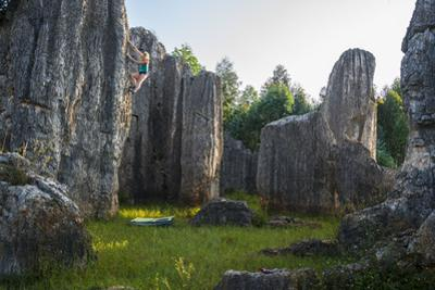A climber ascends a spire in the Stone Forest. by Keith Ladzinski