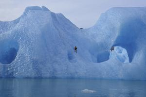 A Climber Navigates Tricky Terrain on a Blue Iceberg Off the Coast of Greenland by Keith Ladzinski