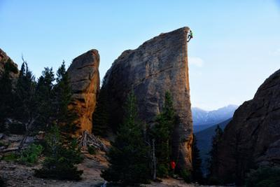 A Climber Reaches the Top of a Rock Formation Near Lily Lake in Estes Park, Colorado by Keith Ladzinski