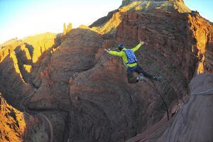 A Man Base Jumps with a Parachute Off a Desert Spire on Fisher Towers by Keith Ladzinski