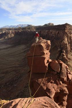 A Man Belays His Climbing Partner on Fisher Towers in Utah by Keith Ladzinski