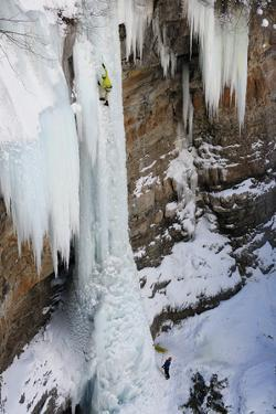A Man Ice-Climbing the Fang, an Ice Formation on the Side of a Cliff by Keith Ladzinski