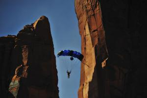 A Man Parachutes after Base Jumping Off a Desert Spire from Fisher Towers by Keith Ladzinski