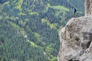 A Man Walks Out onto a Rock Outcrop Overlooking Evergreen Forests by Keith Ladzinski