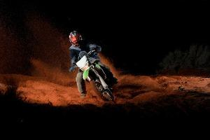 A Motorcyclist Rides on Sand Dunes, Kicking Up Sand Behind Him by Keith Ladzinski
