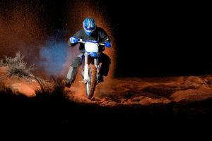 A Motorcyclist Rides on Sand Dunes, with Clouds of Sand and Smoke Behind Him by Keith Ladzinski