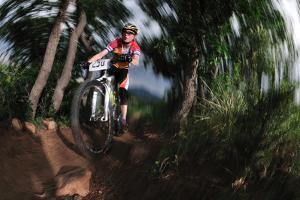 A Mountain Biker Rides on a Single Track Trail Through a Scrub Oak Forest by Keith Ladzinski