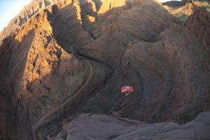 A Person Parachutes after Base Jumping Off a Desert Spire in Fisher Towers by Keith Ladzinski