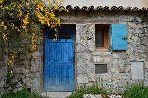 A Stone Building with a Bright Blue Door and Window Shutter by Keith Ladzinski