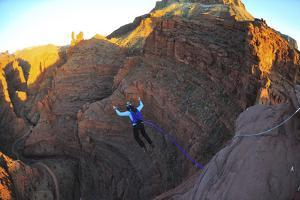 A Woman Base Jumps with a Parachute Off a Desert Spire on Fisher Towers by Keith Ladzinski