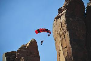 A Woman Parachutes after Base Jumping Off a Desert Spire at Fisher Towers by Keith Ladzinski