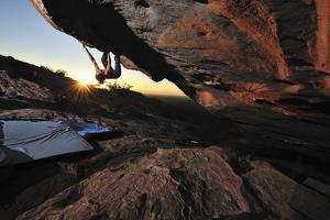 A Woman Rock-Climbing under a Sheer Rock Face by Keith Ladzinski