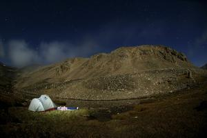 A Woman Sleeps under the Stars at a Campsite in Cederberg Wilderness Area, South Africa by Keith Ladzinski