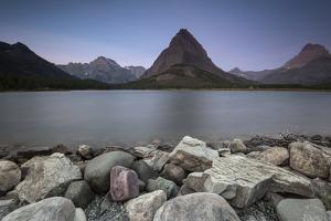 Mountain Peaks Loom Above Swiftcurrent Lake in Montana's Glacier National Park by Keith Ladzinski