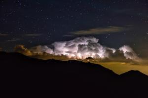 Storm Cloud Looms over the Mummy Range on a Starry Night in Rocky Mountain National Park by Keith Ladzinski
