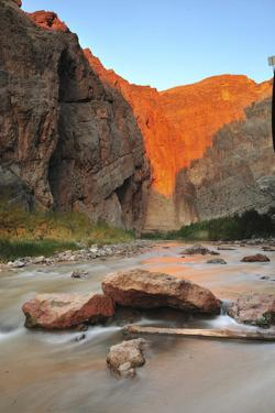 The Virgin River Running Below a Cliff Lit in Sunlight by Keith Ladzinski