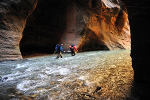 Two Men Hiking Through the Virgin River Narrows in Zion National Park by Keith Ladzinski