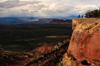 Two Mountain Bikers Pause Atop a Cliff as Storm Clouds Approach by Keith Ladzinski