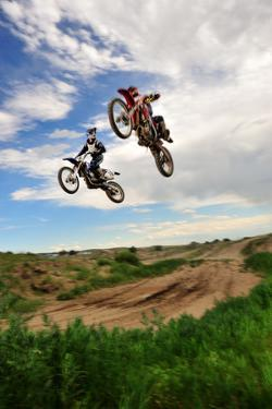 Two Riders Jump in Unison at a Motocross Event by Keith Ladzinski