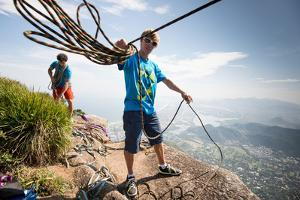 Young Man Standing on Top of the Mountain Holding Rope for Slacklining by Keith Ladzinski