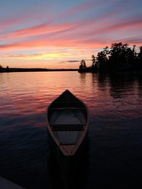 Canoe Floating in Lake During Sunset by Keith Levit