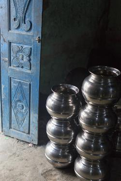 Stacks of Stainless Steel Pots Sit Near an Open Blue Door by Kelley Miller