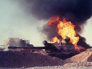 Iraqi Tank Burning While US Army Convoy Drives Past into Iraq During Gulf War by Ken Jarecke