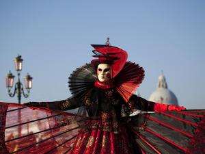 Venice, Veneto, Italy, a Mask in Costume on the Bacino Di San Marco with the Cupola of Santa Maria  by Ken Scicluna