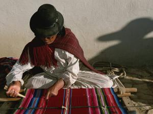 A Bolivian Woman Weaves Brightly Colored Fabric on a Loom by Kenneth Garrett
