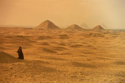 A solitary figure in the desert at Abusir. Giza is in the distance. by Kenneth Garrett