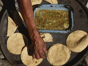 A Vendor Displays a Sample of Local Mexican Cooking with Tortillas by Kenneth Garrett