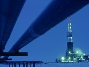 Alaska Oil Pipeline and Oil Rig at Night by Kenneth Garrett
