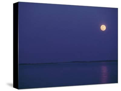 Purple Sky and Moon over a Body of Water by Kenneth Garrett