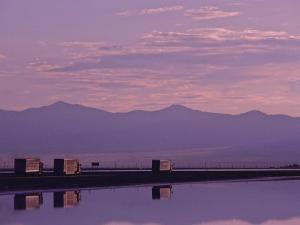 Trucks on the Highway Reflected in Great Salt Lake, Utah by Kenneth Garrett