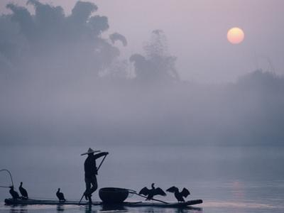 A Fisher Uses Cormorants to Capture Fish from the Li River at Sunrise
